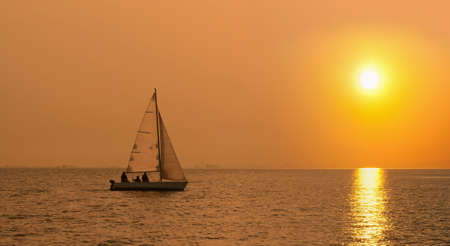 Sailing boat in the sea at sunset  photo