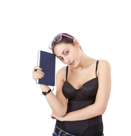 Pretty young girl in black corset with book, pen and glasses isolated on white background  photo