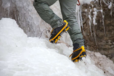 crampons: Pair of alpinist boots in crampons on ice