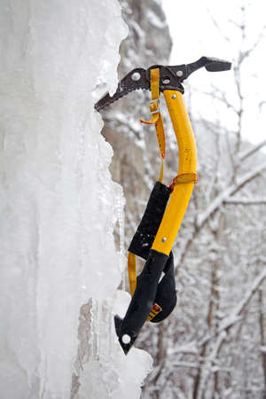 carny: Climbing ice ax in the white ice fall  Stock Photo