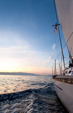 deportes nauticos: Velero en el mar al atardecer  Foto de archivo