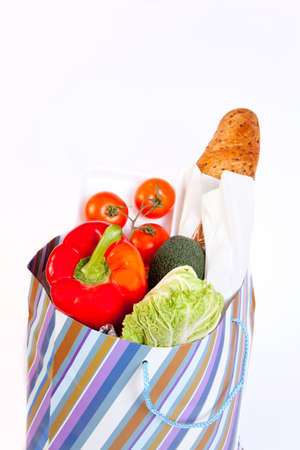 Paper bag full of vegetables isolated on white background  photo