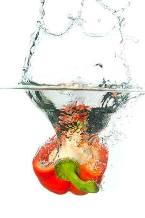 pimenton: Piment�n rojo en agua splash aislada sobre fondo blanco