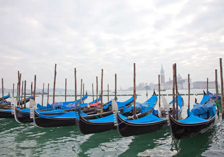 Gondolas with blue cover in Venice at the pier  photo