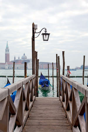 Gondola at the end of the bridge with blue cover in Venice at the pier Stock Photo - 9037044