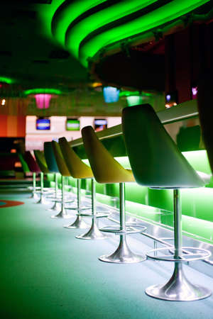 stool: Chairs in row in bar with green lights