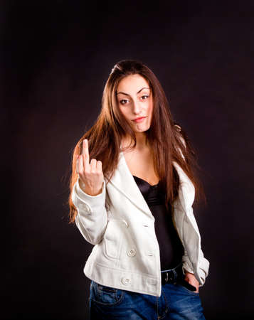 Pretty young girl showing middle finger on dark background  photo