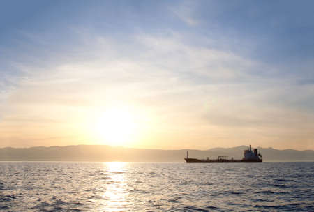Bulk-carrier ship at sunset in the sea photo