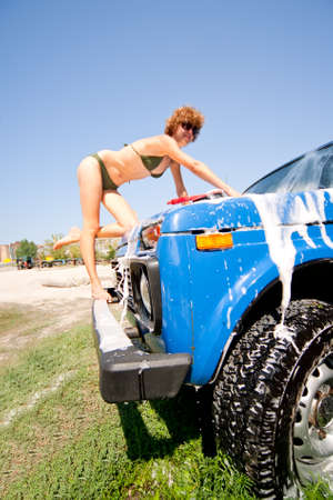 Girl in bikini washing car with selective focus on wheel  photo