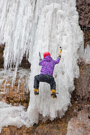 Man with ice axes and crampons climbing on icefall  photo