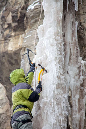 Man with ice axes climbing on icefall