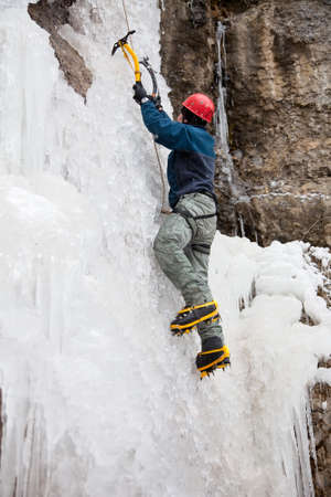 ice climbing: Man with ice axes and crampons climbing on icefall  Stock Photo