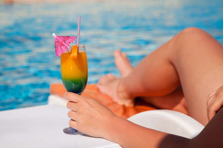 poolside: Woman hand with cocktail glass near swimming pool  Stock Photo