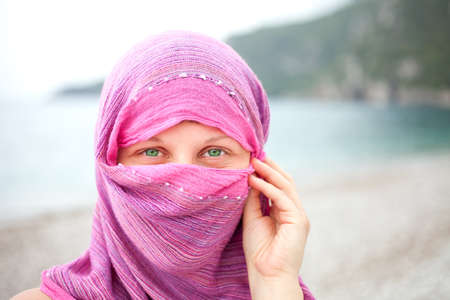 Beautiful girl with face covered by red scarf looking with eyes photo