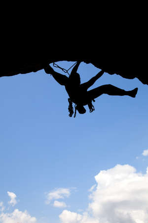 Rock climber silhouette in a sunny day climbing high Stock Photo - 9560259
