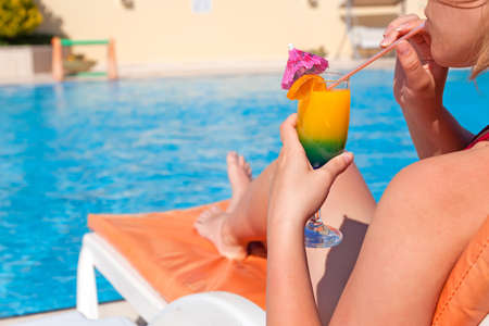 Woman hand drinking cocktail with plastic straw near swimming pool  photo
