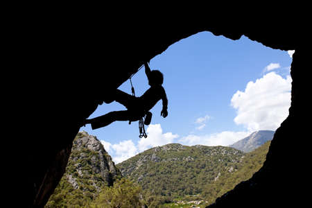 Rock climber silhouette in a sunny day climbing high Stock Photo - 9948798