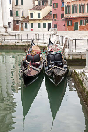 Two gondola in Venice at the pier and buildings photo