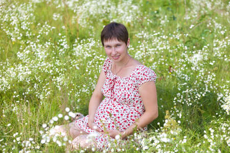 Pregnant woman sitting in chamomile background Stock Photo - 10199891