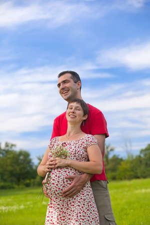 Husband hugs his pregnant wife outdoor Stockfoto