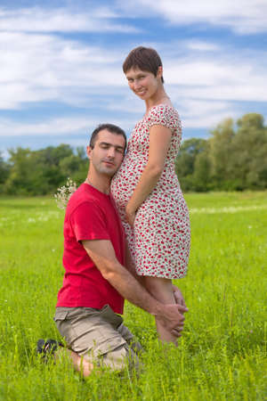 Husband taking care of his pregnant wife on the green meadows photo