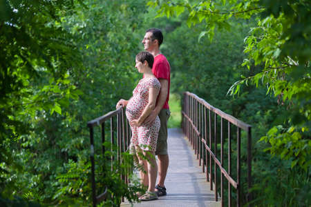 Husband with his pregnant wife on the bridge in green forest photo