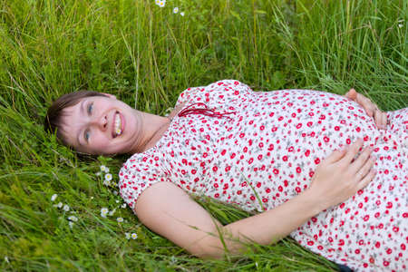 Pregnant woman lie in chamomile and grass background Stock Photo - 10338602