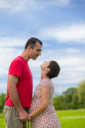 oudoor: Husband looks at his pregnant wife oudoor