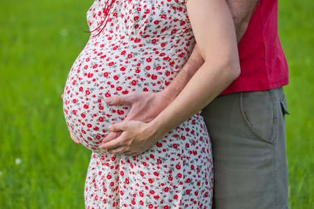 Husband hands on pregnant woman belly, outdoor shooting