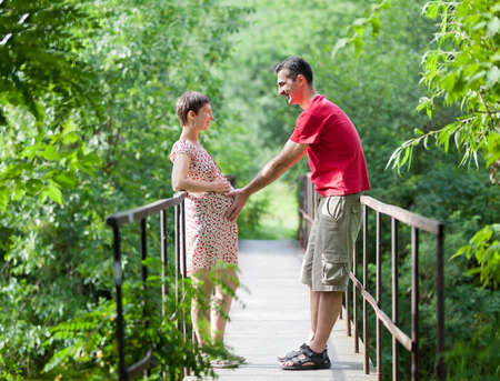 Husband with his wife on the bridge in green forest  photo