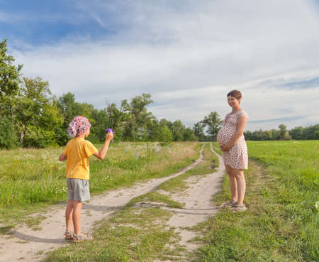 Small boy making soap bubbles with his regnant mother in the green field  photo