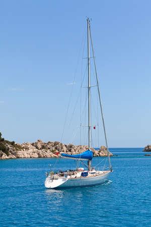 White sailboat in turkish bay on blue sea Stockfoto