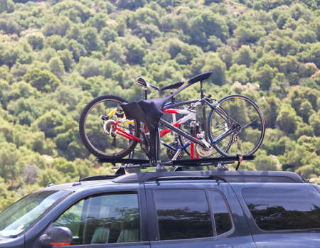 Three bicycles on the top of offroad car near forest