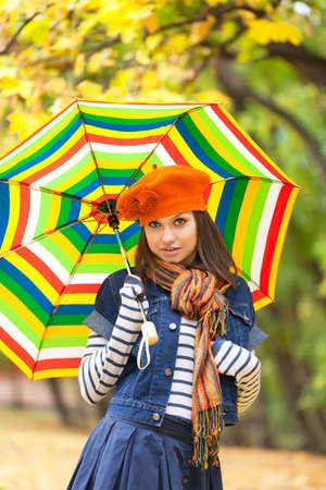 Young pretty girl with striped umbrella closeup view photo