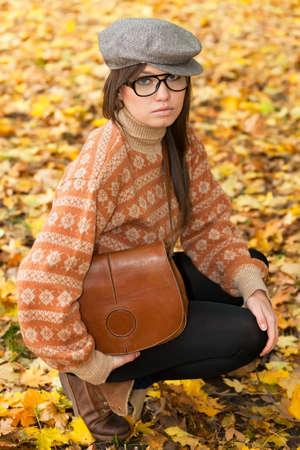 Sad young girl with handbag sitting on yellow autumn leaf background photo