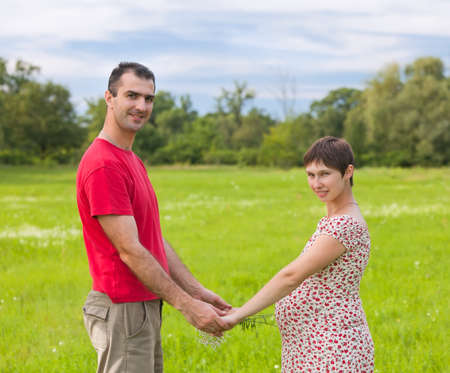 Husband with his pregnant wife on the green meadows photo