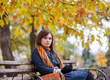 Young woman sitting on the bench in autumn park  photo