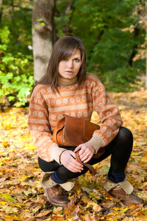 Young girl with handbag sitting on yellow autumn leaf background  photo