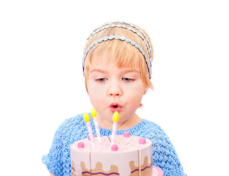 Pretty little girl blowing on candles in the cake isolated on white background