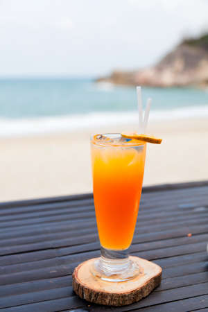 Orange juice in glass with ice, straw and fruit slice on ocean beach background  photo