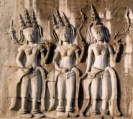 Three dancing apsara on the wall in Angkor Wat, Siem Reap, Cambodia  photo
