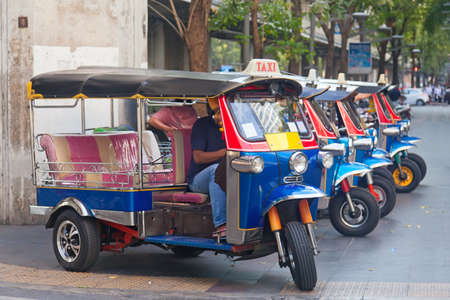 Line of tuktuks with driver on Bangkok street, Thailand Stockfoto