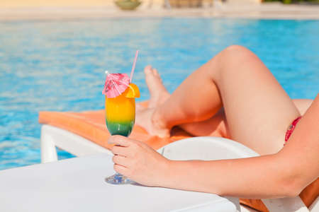Woman hand with cocktail glass near swimming pool  photo