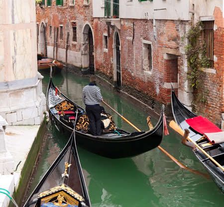 Gondola in Venice channel with gondoliero  Stock Photo