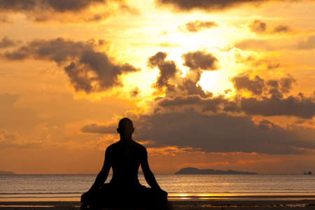 yoga sunset: Man silhouette doing yoga exercise at sunset beach  Stock Photo
