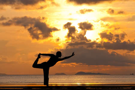Man silhouette doing yoga exercise natarja at sunset beach Stockfoto