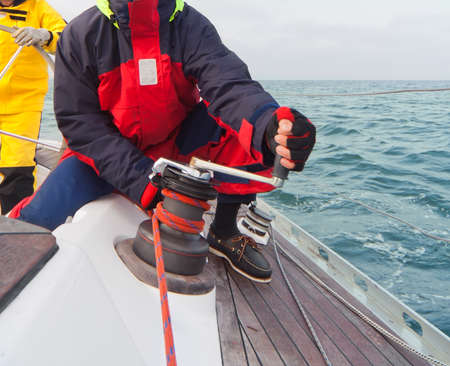 Man holding winch with rope on sailing boat Standard-Bild