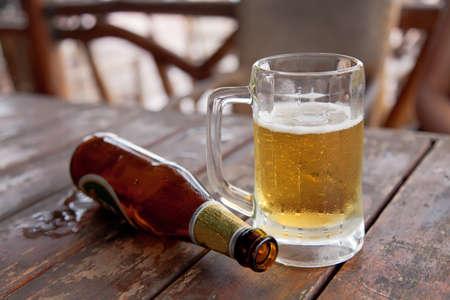 botellas de cerveza: Botella vacía y el vaso de cerveza en la mesa de madera Foto de archivo