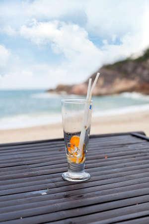 Empty glass with ice, straw and fruit slice on ocean beach background  photo