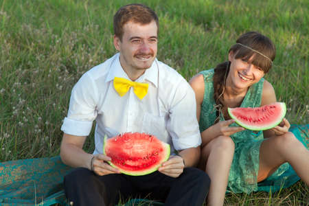 Young couple eating watermelon at picnic  photo